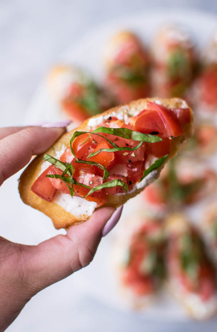 holding a piece of Italian Bruschetta