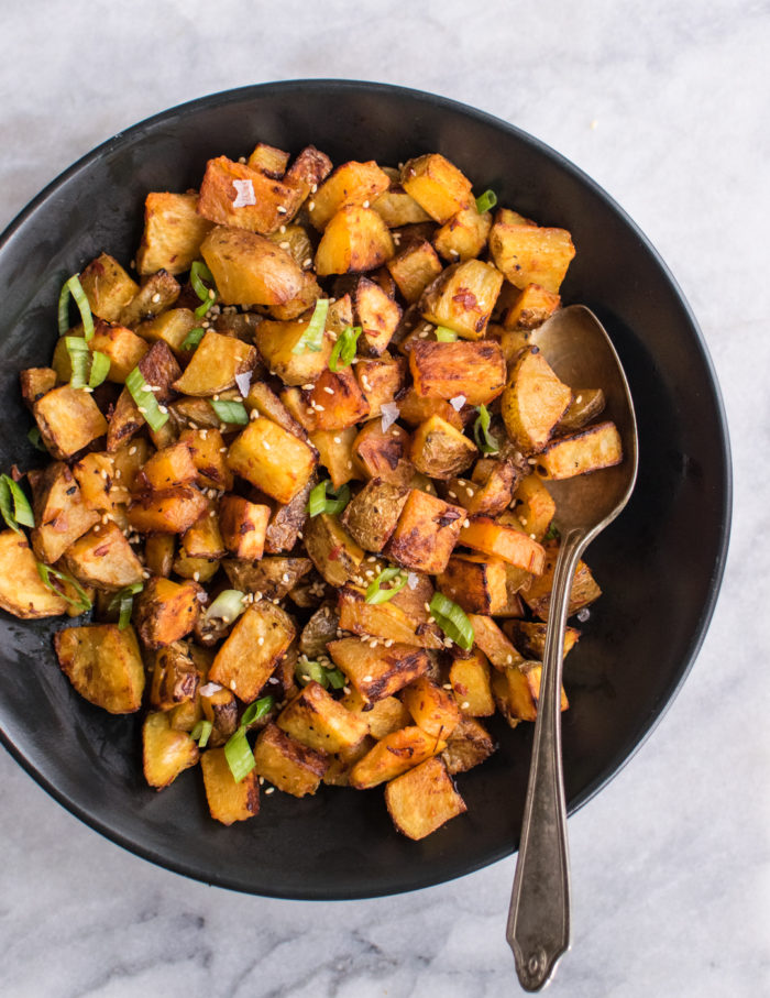 A bowl of spicy roasted potatoes with tahini sauce drizzled on top. Served with scallions and sesame seeds.